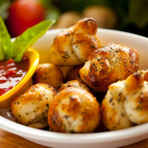 A classic snack, our garlic knots are strips of pizza dough tied in a knot, baked, and then topped with melted butter, garlic, and parsley
